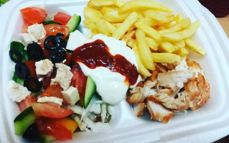 Гирос на тарелке с картофелем фри и с греческим салатом