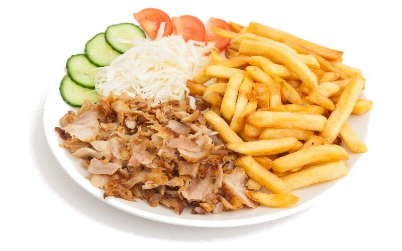 Гирос на тарелке с картофелем фри и овощами