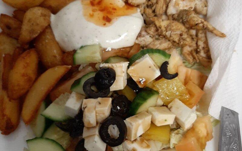 Гирос на тарелке с картофельными дольками и с греческим салатом