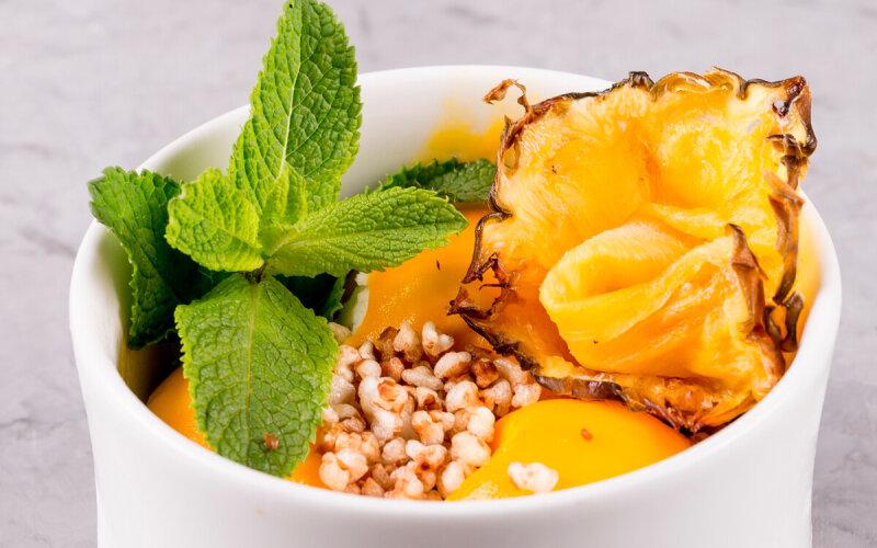 Мороженое с соусом из манго, вяленым ананасом и чипсами из гречки