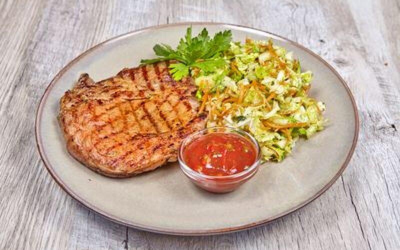 Стейк из свинины, подается с соусом и зелёным  салатом