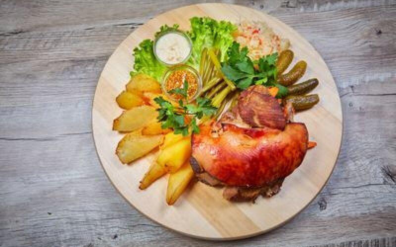 Рулька свиная, запеченная  в медовом маринаде, гарнированная картофельными дольками и соленьями.
