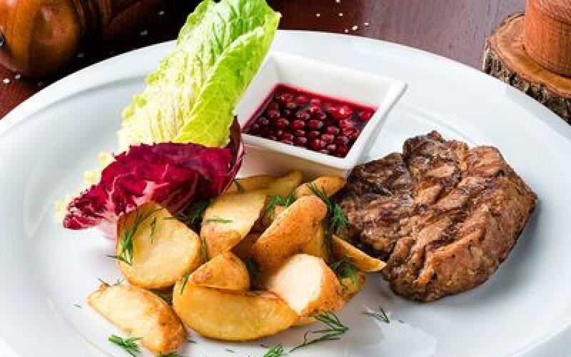 Стейк из свинины с брусничным соусом и картофельными дольками